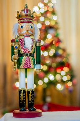 A nut cracker stands in front of a christmas tree